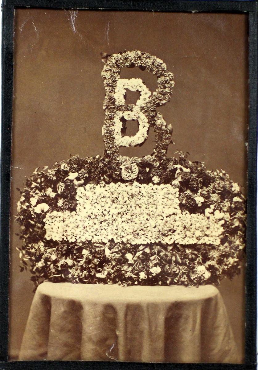 Blomsterdekorasjon med monogram.
