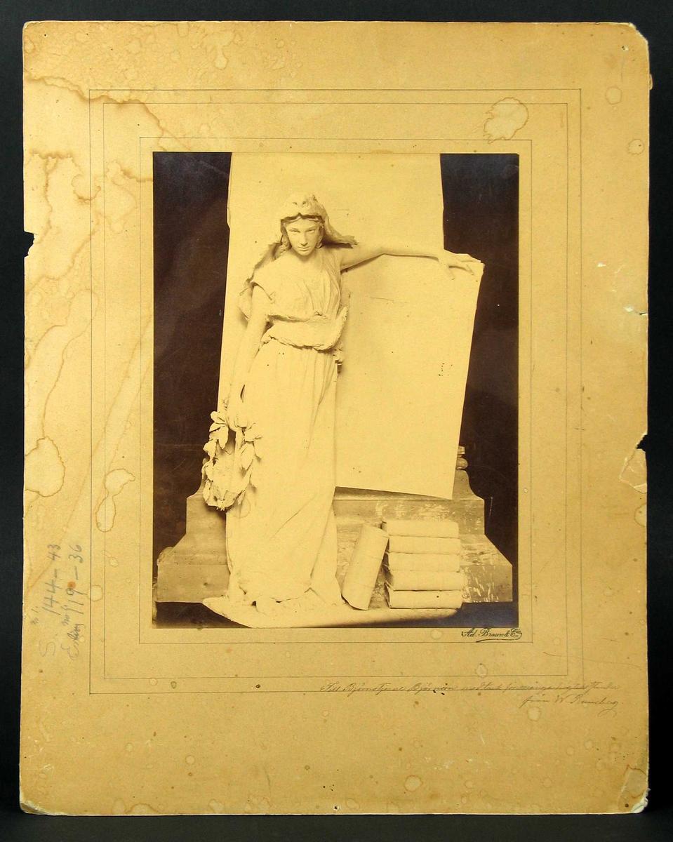 Kvinne med krans i hånden og armen over en tavle. Ved føttene er det stablet bøker.