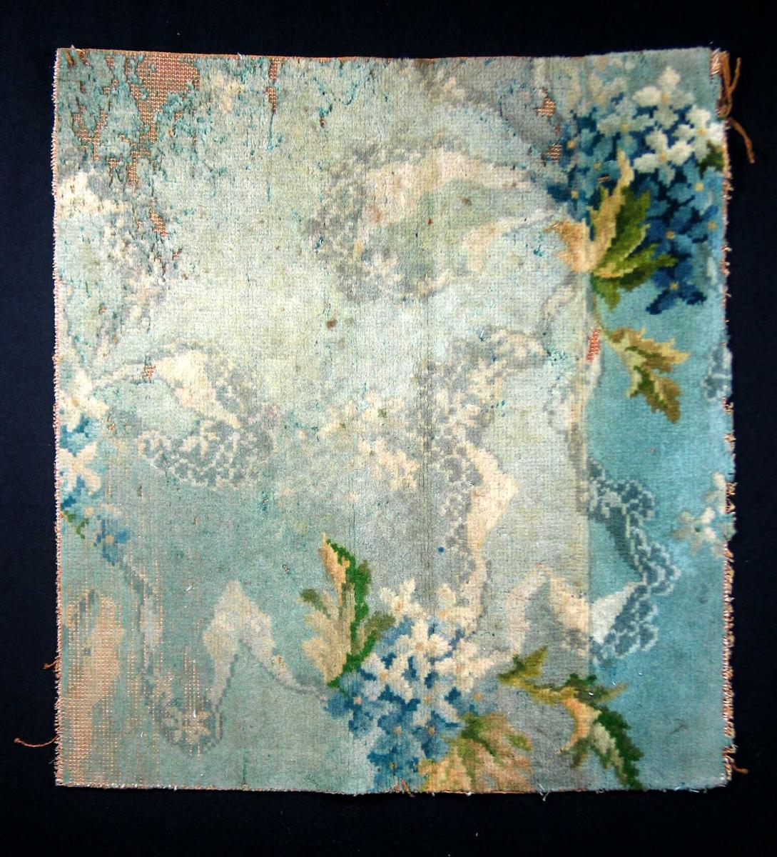 Fragment av golvteppe i ullfloss. Motivet er blomster og bladverk i nyanser av blått, grønt, beige og hvitt. Maskintilvirket.