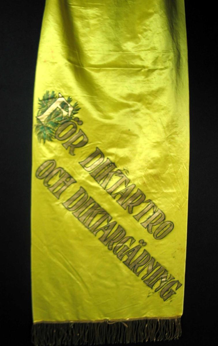 Begravelsessløyfe i gul silke med skrift og frynser i gull.