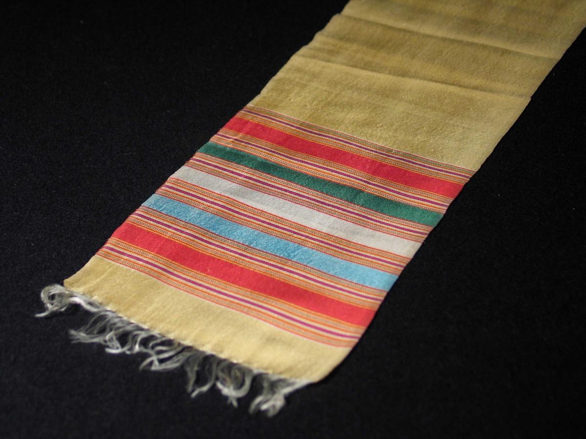 Gult bånd i natursilke med flerfargede striper i endene. Hvite frynser ytterst dannes av renningen. Overkastet.