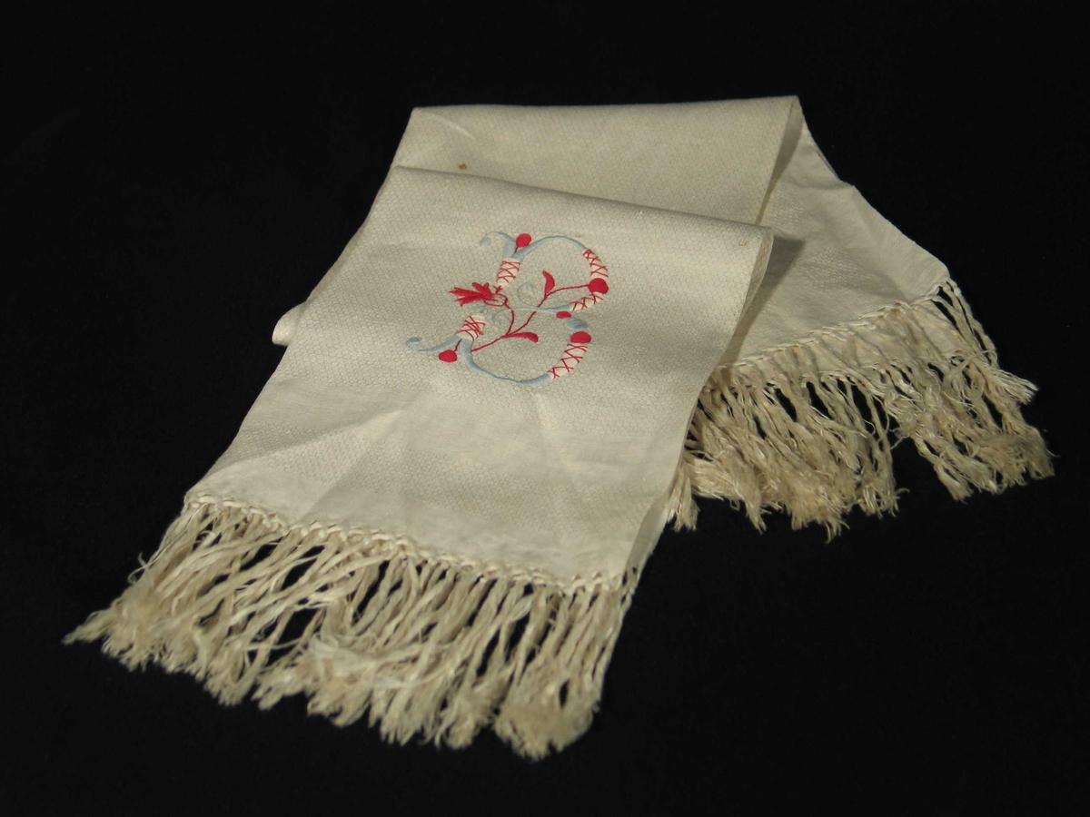 Håndkle i vaffelmønstret lin med frynser. Brodert monogram i rødt og blått.