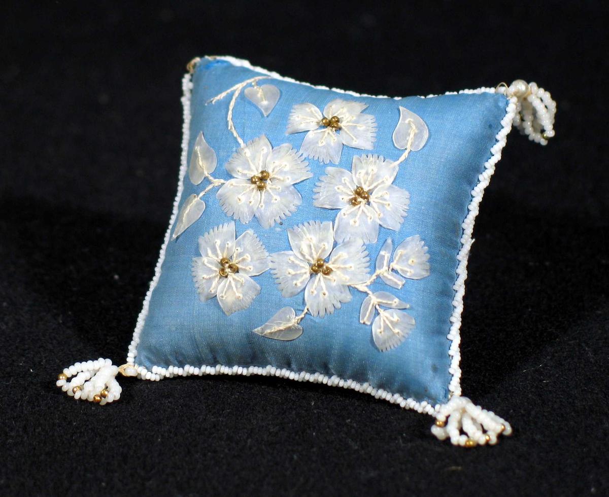 Nålpute i blå silke påsydd blomstermønster i tynt gjennomsiktig glasslignende stoff. Det er perlesnor langs kantene med dusker i hjørnene. En mangler.