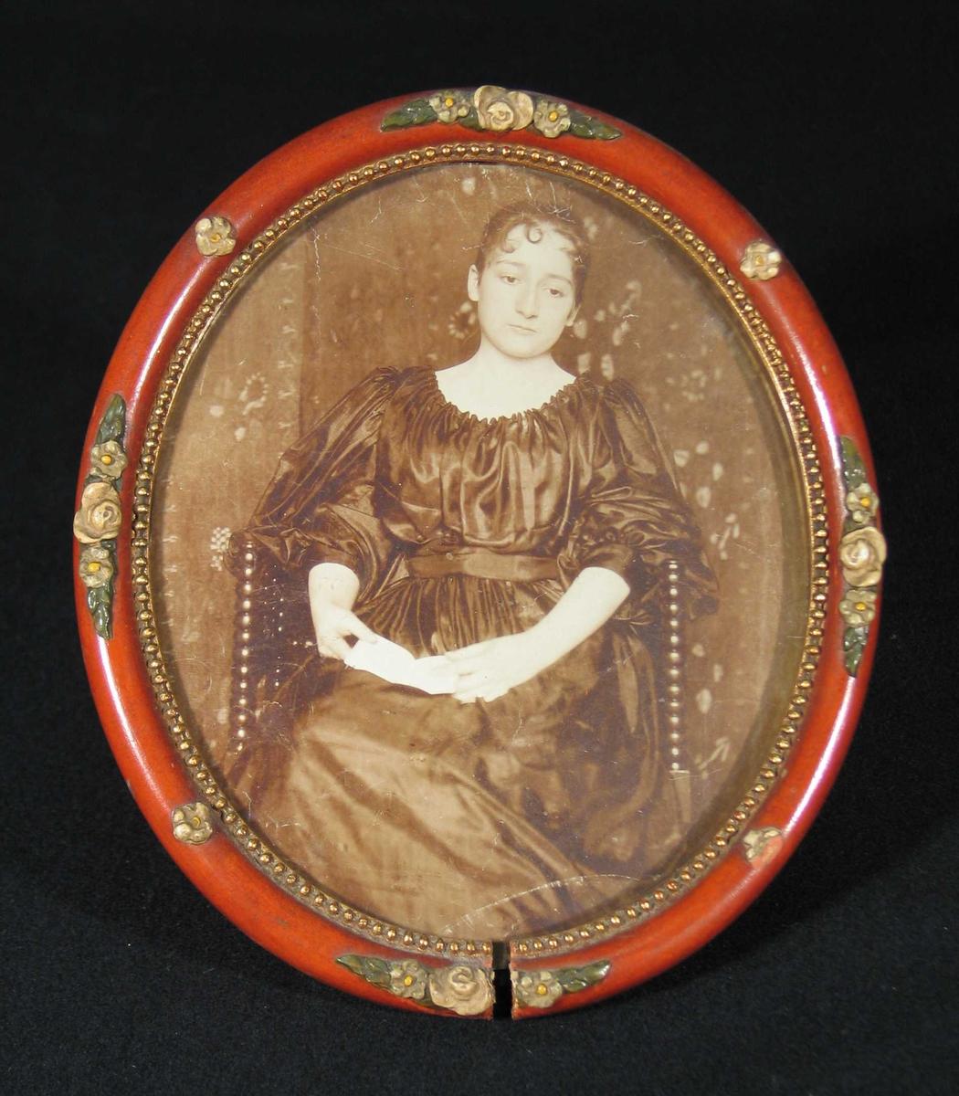 Ung kvinne i mørk kjole sitter med åpen bok i fanget.