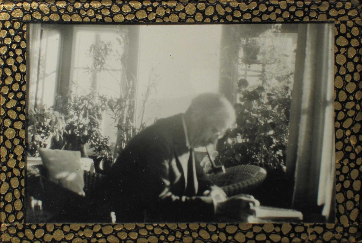 Mann sittende på en glassveranda, bøyd over papirer med pipe i munnen.