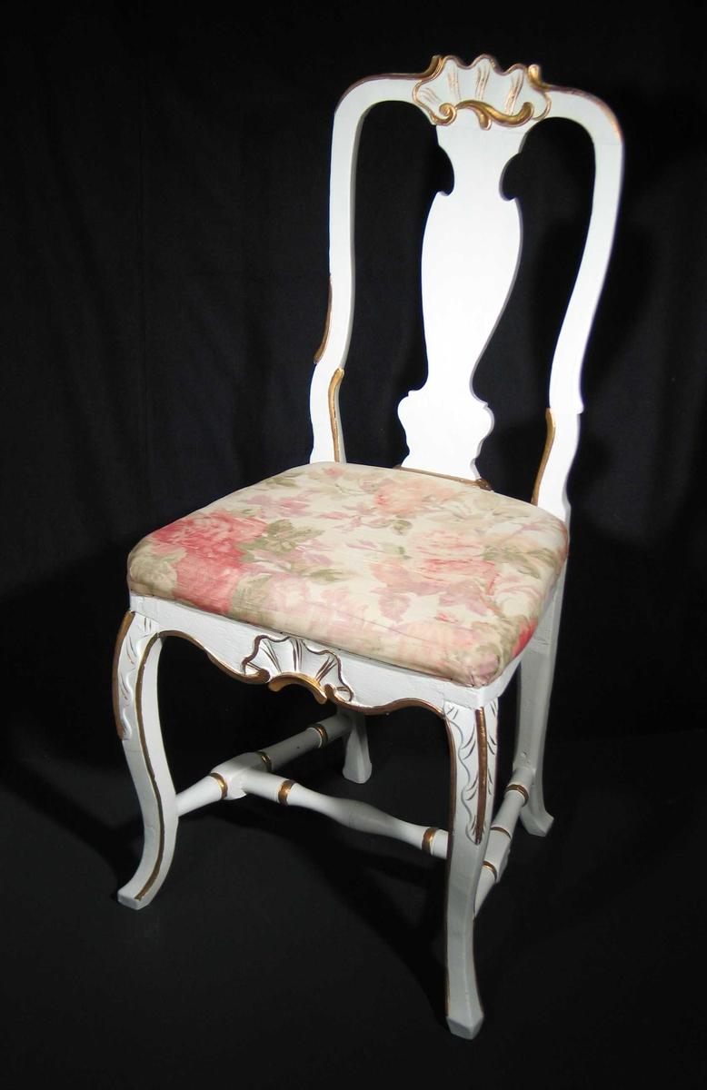 Hvitmalt stol i bjørk med stoppet sete. Den har utskårne rocailler på toppstykke og sarg. Ryggen har buede sider med symmetrisk midtfjøl. Forbenene er svungne med bølget utskjæring på kne. Stolen har dreide sprosser. Gullmalt dekor. Setet er trukket om i blomstret bomullskretong.