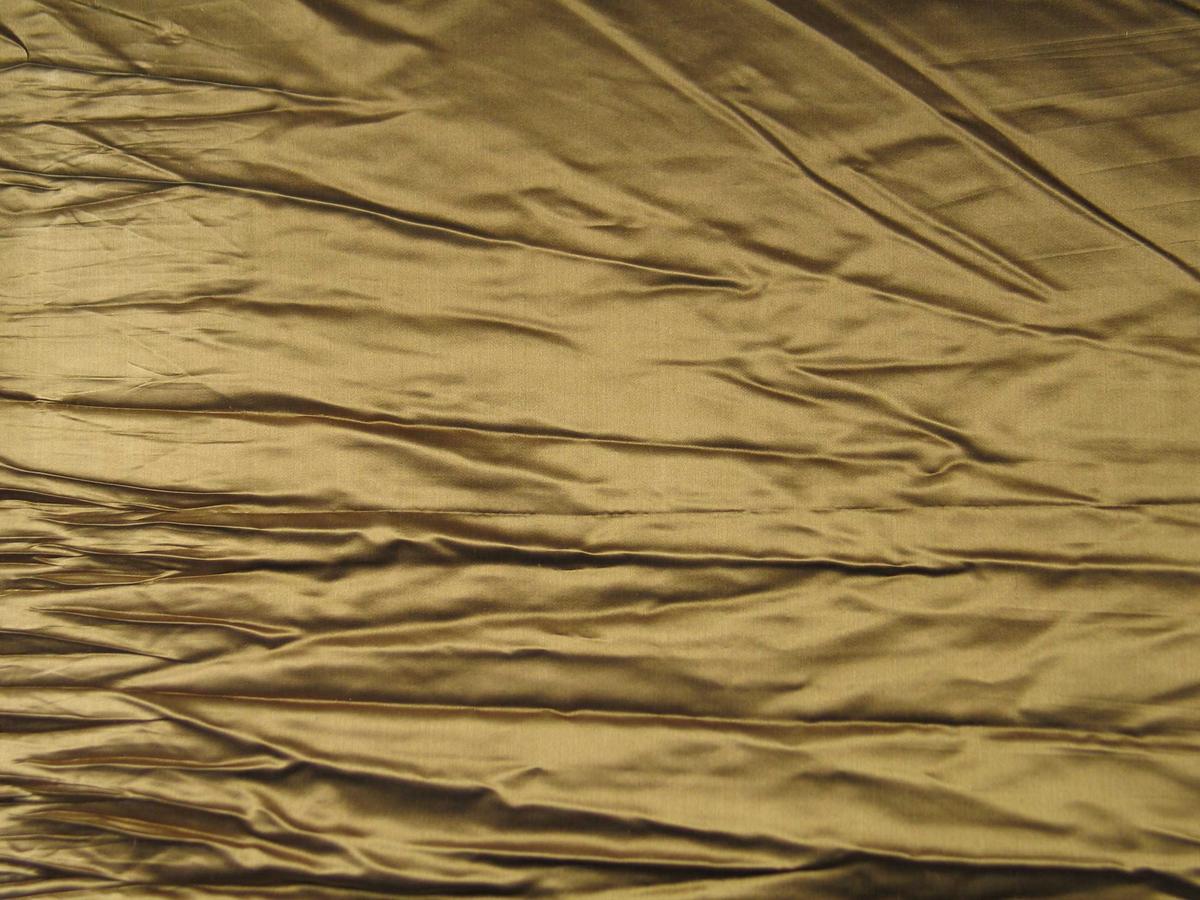 Rest av gullbrun kunstsilke. Jare i begge sider med sølvfarget kant.