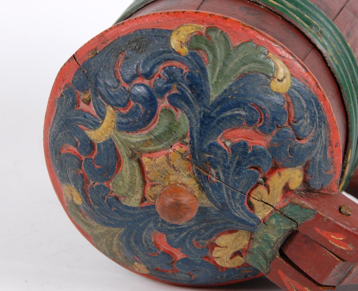 Kanne av furustaver. Lokk med akantusskurd malt i grønne, gule og blåe farger. Kuleformet lokkgrep. Korpus med fire grønnmalte gjorder oppe og en nede (opprinnelig tre). Hanken er utskåret av en av stavene, ender nederst i en plate med bladmotiver.