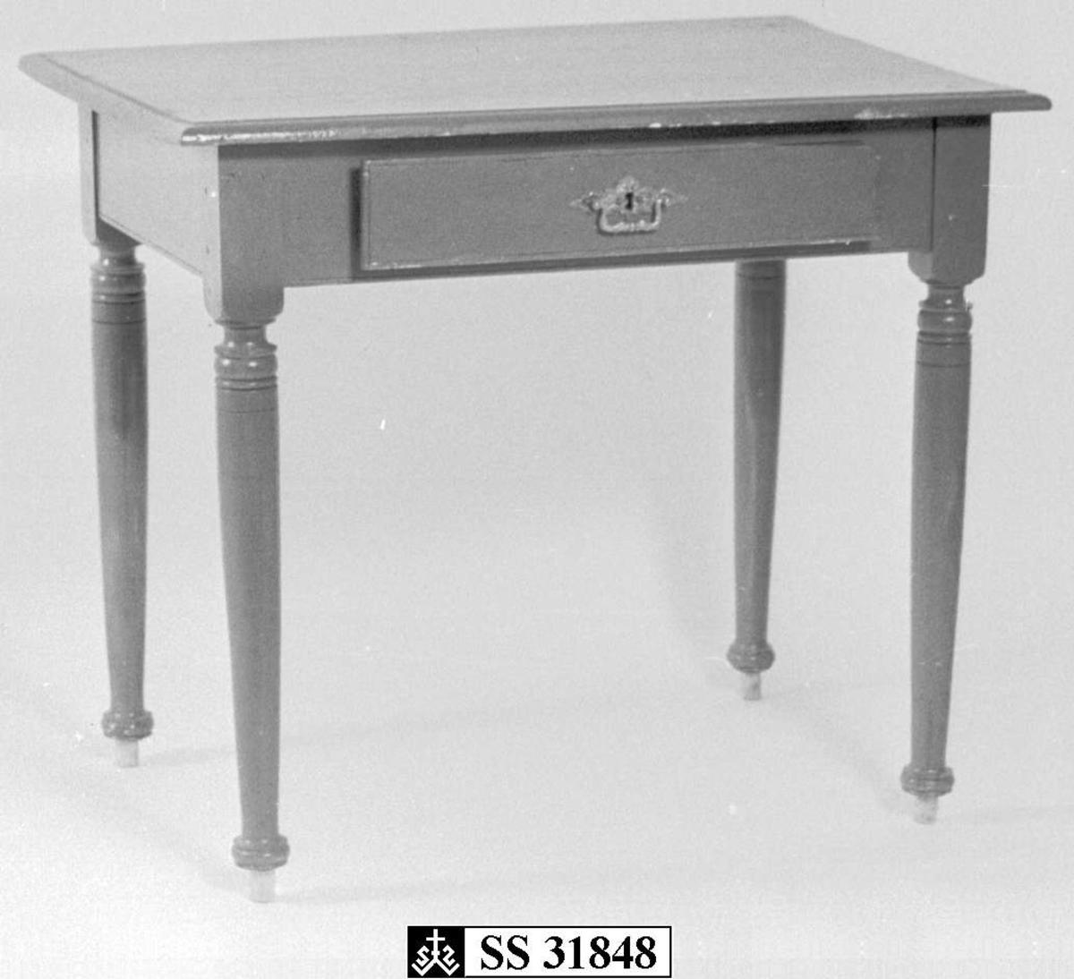 Brunmalt bord med dreide bein og plate med avfaset kant. Skuff med messing håndtak og lås, men nøkkel mangler. Knotter nederst på beina, muligens for å gjøre bordet noe høyere.