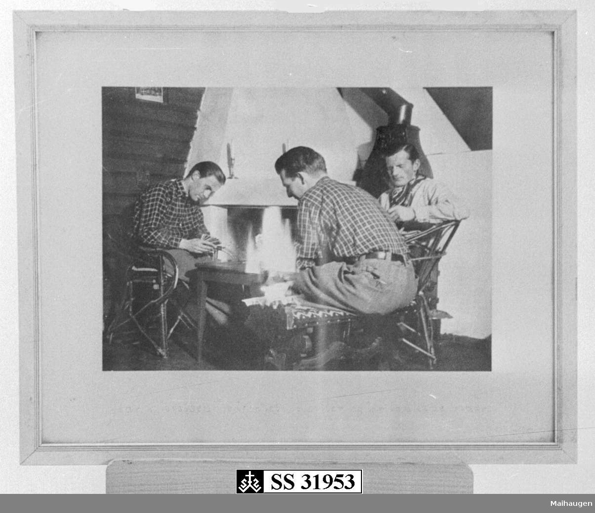 Tre menn ved peisen som spiller kort.