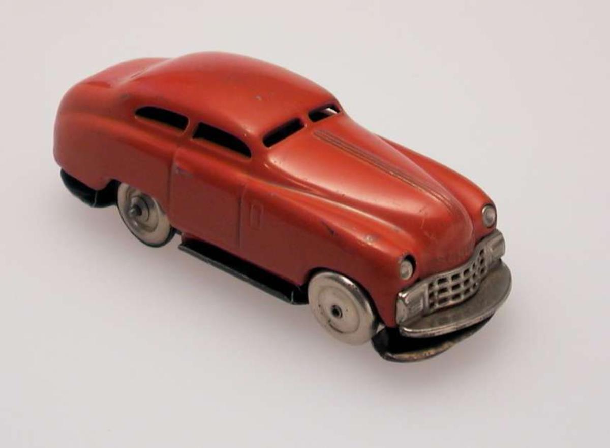 Lekebil til å trekke opp i metall med gummihjul. Det mangler gummi på tre av hjulene. Bilen er rød med metallfarget grill og runde frontlykter. Bilen er noe defekt. Understellet har løsnet fra overdelen. Bildekkene er ikke hele.Nøkkelen til å trekke opp bilen mangler også.