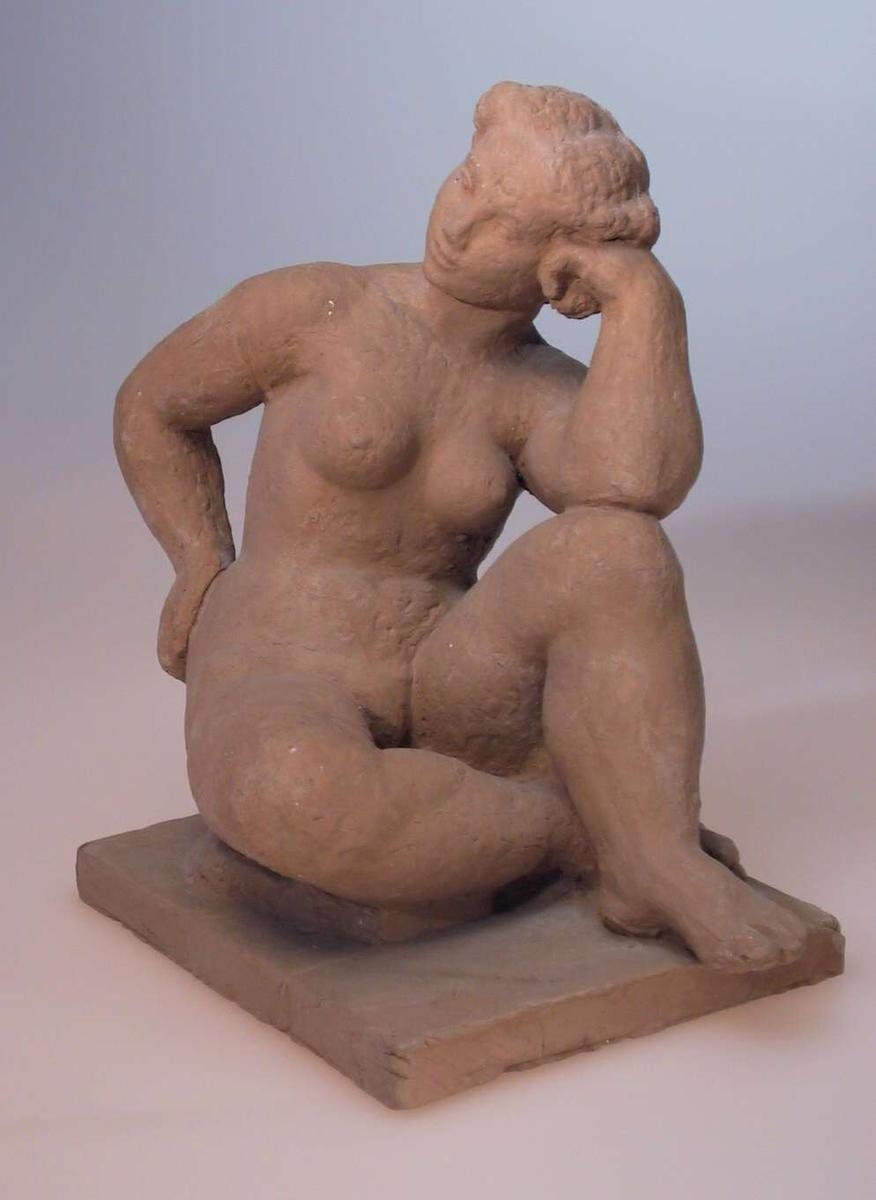 Sittende kvinnelig aktmodell av terrakotta. Kvinnen sitter med høyre beinet bøyet under venstre kne. Venstre albue støttes på venstre kne, og venstre arm støtter hodet.