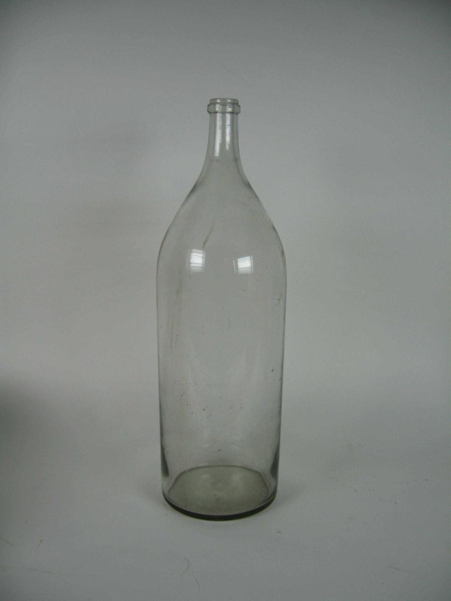 Stor sylindrisk flaske med smal hals. Laget av klart glass, til bruk med kork.
