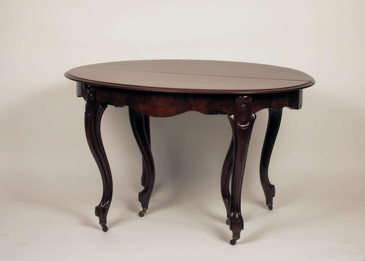 Ovalt spisestuebord med uttrekk og ileggingsplate.Det er trillehjul under bena. Materialet er mahogny. Plate og ben i heltre. Sarg i heltre furu finert med mahogny finér. Ileggingsplaten er  i heltre.