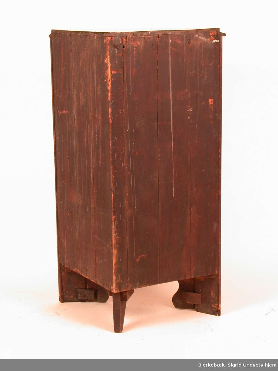 Hjørneskap med en skuff øverst og en skapdel under. Skapedelen har tre hyller. Materielet er mahognyfinér på heltre furu.