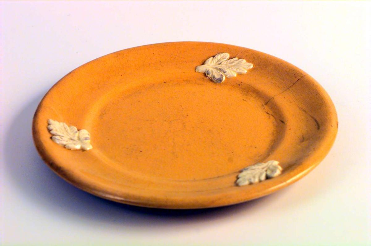 Gul asjett. Den har tre hvite blader som dekor. Det er en sprekk i glasuren. Det er ingen produksjonsmerker på asjetten.