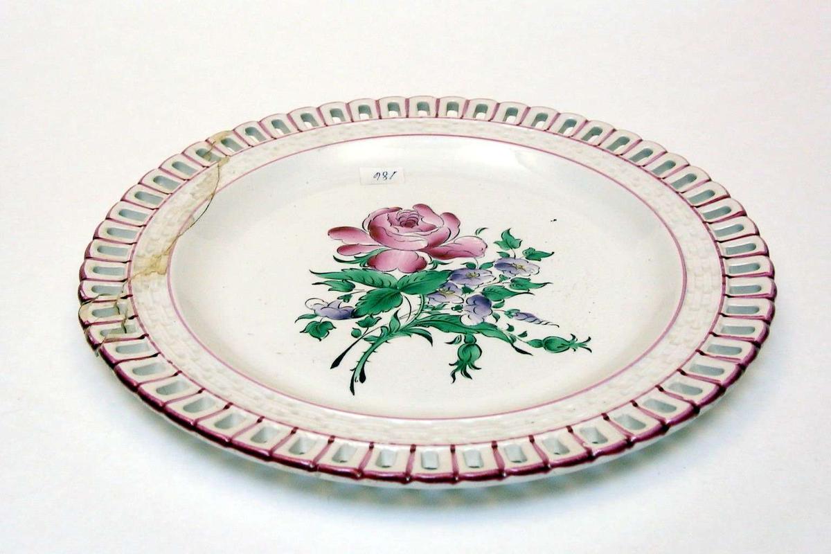 Tallerken i keramikk med kremfarget glasur og med blomsterdekor. Den har 'hullfallskant'. Den er stemplet Demi-porcelaine, Luneville, Made in France, med bokstavene K og G rundt en krone.