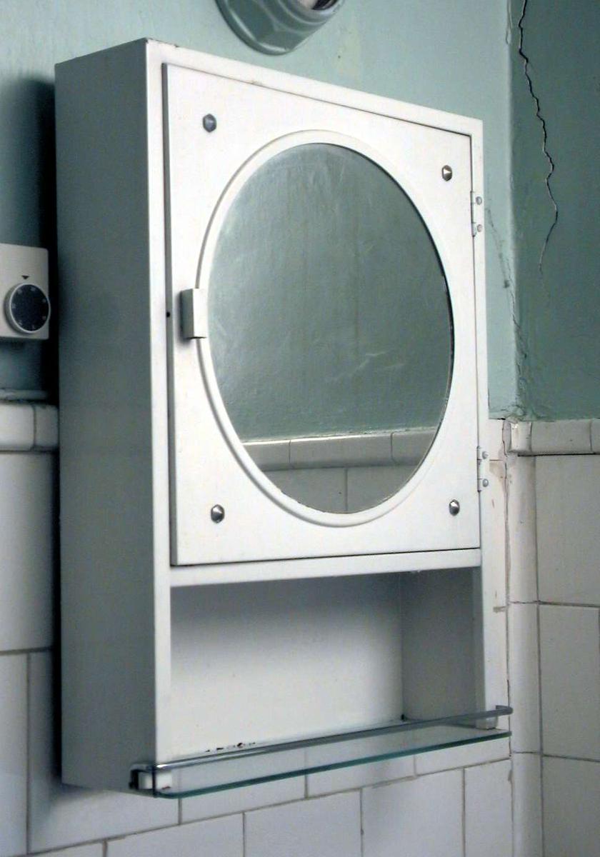 Hvitt medisinskap med en glasshylle under. Skapet har rundt speilglass i døren. Inne i skapet er det syv små hyller og et lite skap med dør.