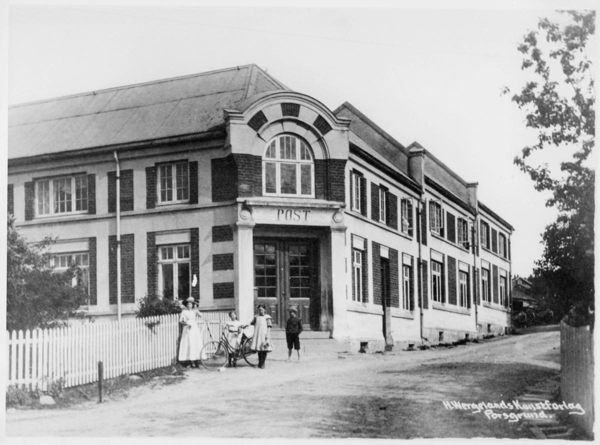 postkontor, eksteriør, Ulefoss, Cappelens hus, posthusgården, murbygning med inngangsparti på enden av bygget, en kvinne og tre barn står utenfor, sykkel