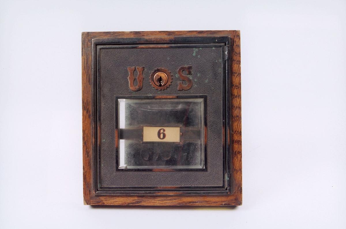 Postboksdør i metall med glassvindu.