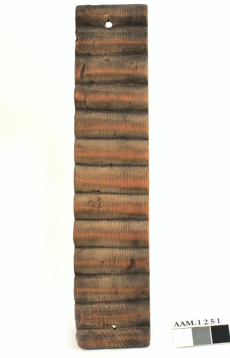 Vaskebrett eller tovebrett. Skåret av tre, muligens furu.   Bølget overside, huller i hver ende.  På baksiden innskåret årstallet   1770.  Tilstand okt. 1960: Ubetydelig markspist.