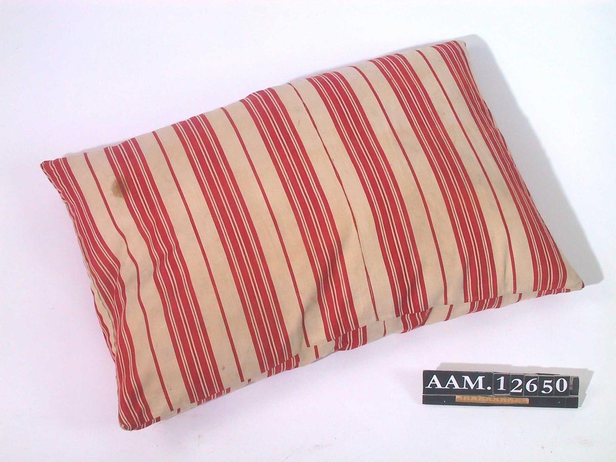 Pute.   Stripet   bolster,  rødt og hvitt.   Rektangulær pute med striper på tvers  i brede felt med en enkelt rød  stripe imel10m. En stor lapp  i samme stoff på den ene siden.   Tilstand: god.