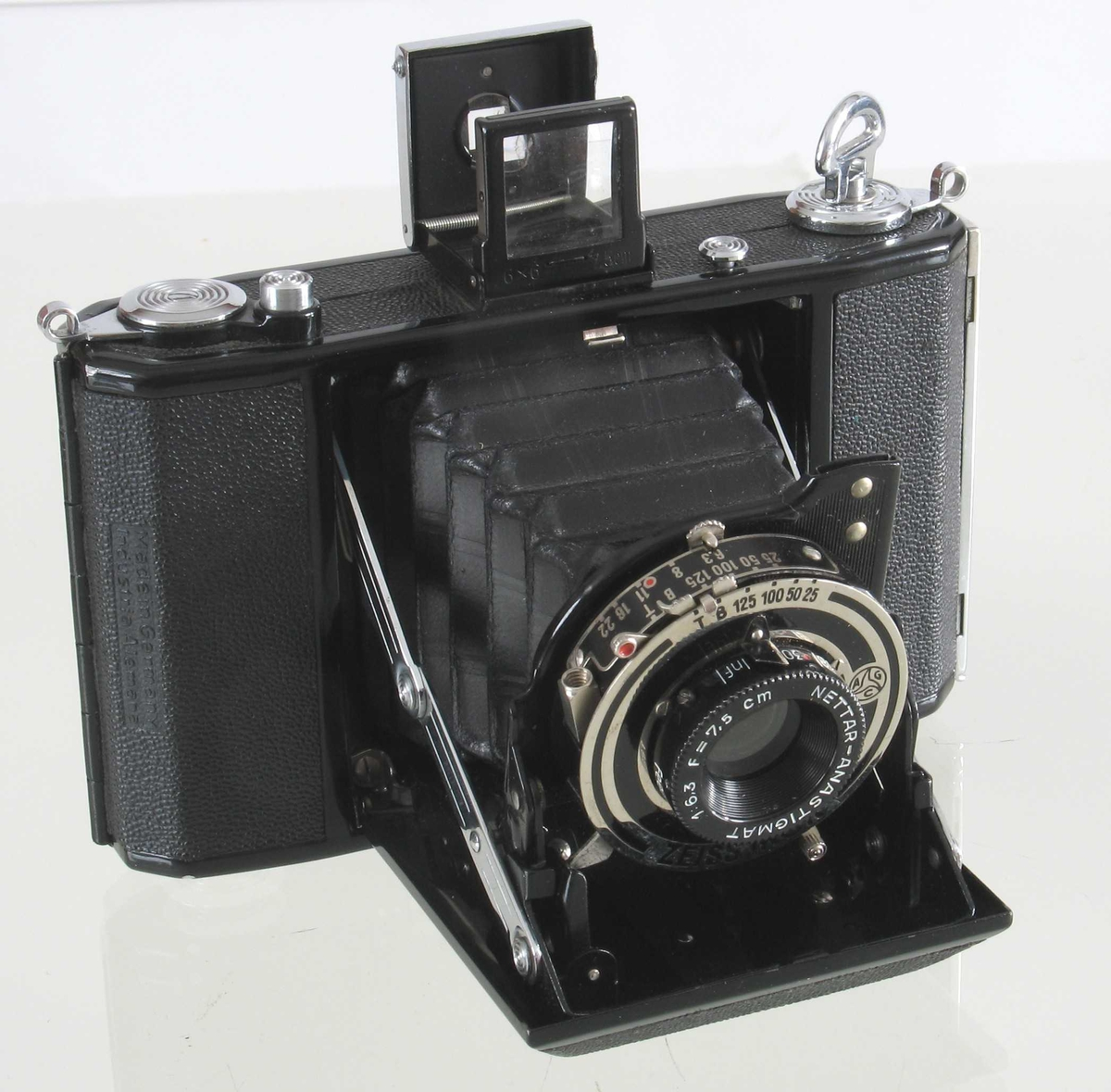 """Fotoapparat i etui  """"Telma"""", Zeiss Ikon Datering: 1930-årene a)Apparat, sort  bakelitt,  forkrommete ståldeler/skruer  H. med sikte 8,5 L.13,5 Dybde 4,3  Smal rektangulær hovedform med avfasede hjørner. Foldeapparat, linsen merket  Zeiss Ikon Telma.  Nettar, Anastigmat. 1:6,3 F = 7,5cm. Innvendig etikett:  Zeiss Ikon Film, med filmeske i farger. b) Skinnpose, sort, med glidelås i den ene kortende. L.ca.20 B.Ca. 10,5"""