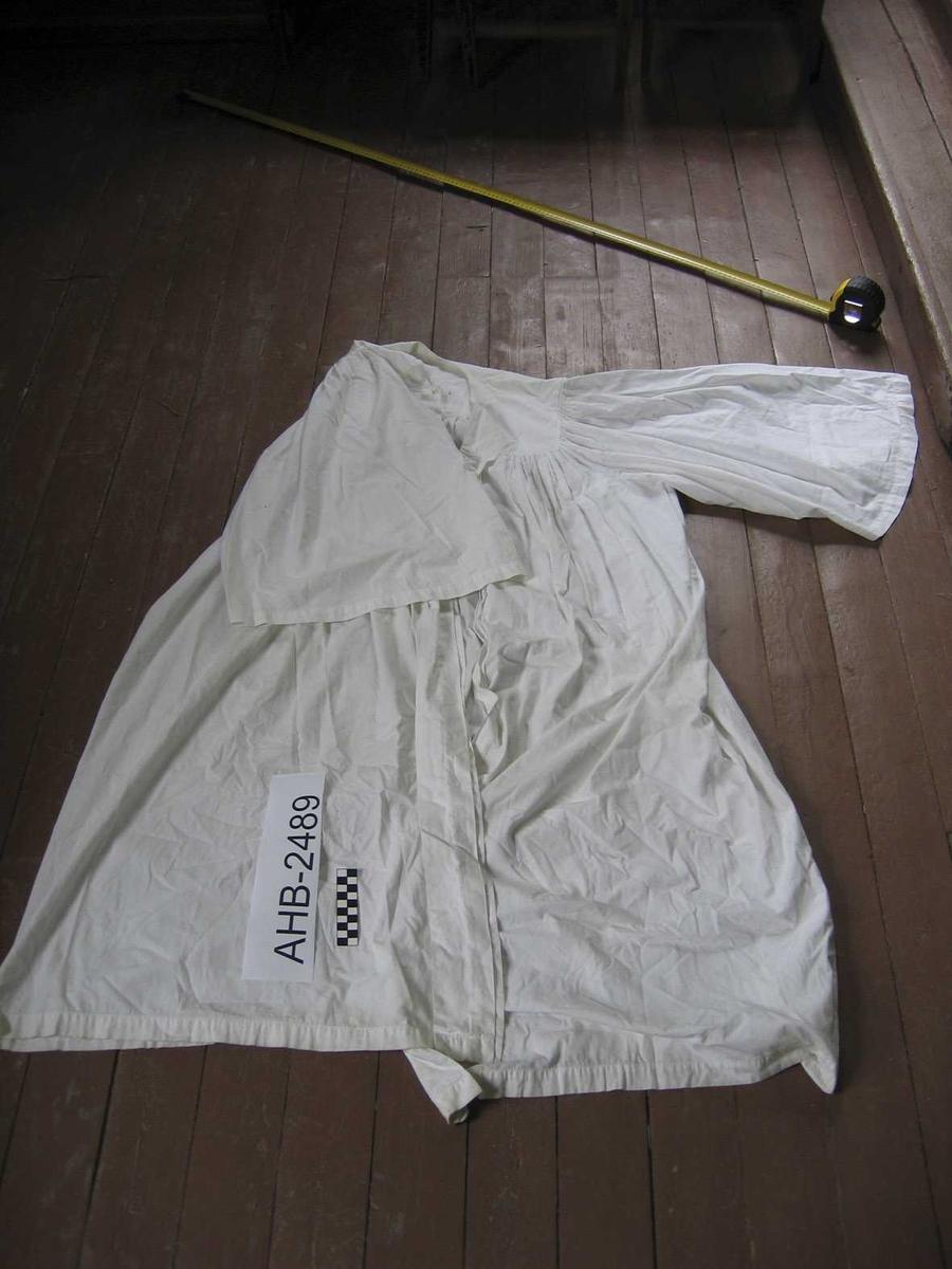 """Hvit """"frakk"""" i tynt bomullstoff beregnet på å bæres over svart prestekjole. Noe skitten (brukt)"""