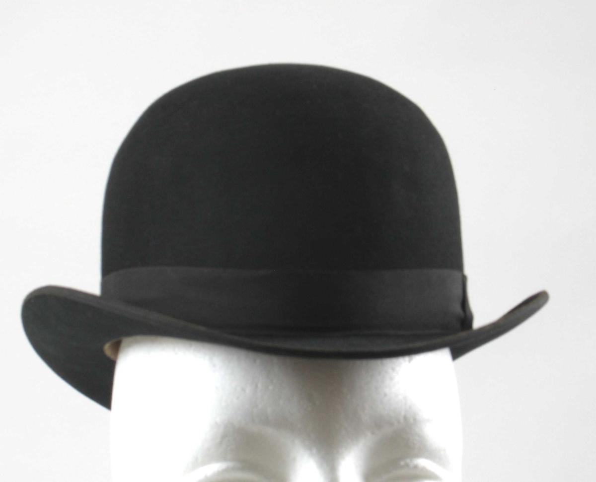 Bowlerhatt, trolig av ull, med for av silke og dtaljer i lær. Rund pull, kort brem bøyd oppover på hver side. Hattebånd knyttet i sløyfe ved den ene siden.