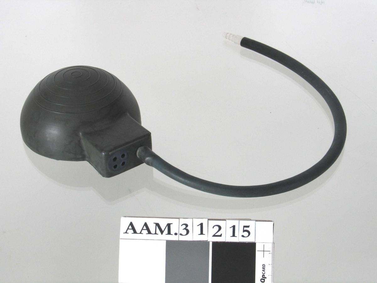 Halvkuleformet pumpe med kvadratisk utstikker på den ene siden, i denne en slange med munnstykke i enden.