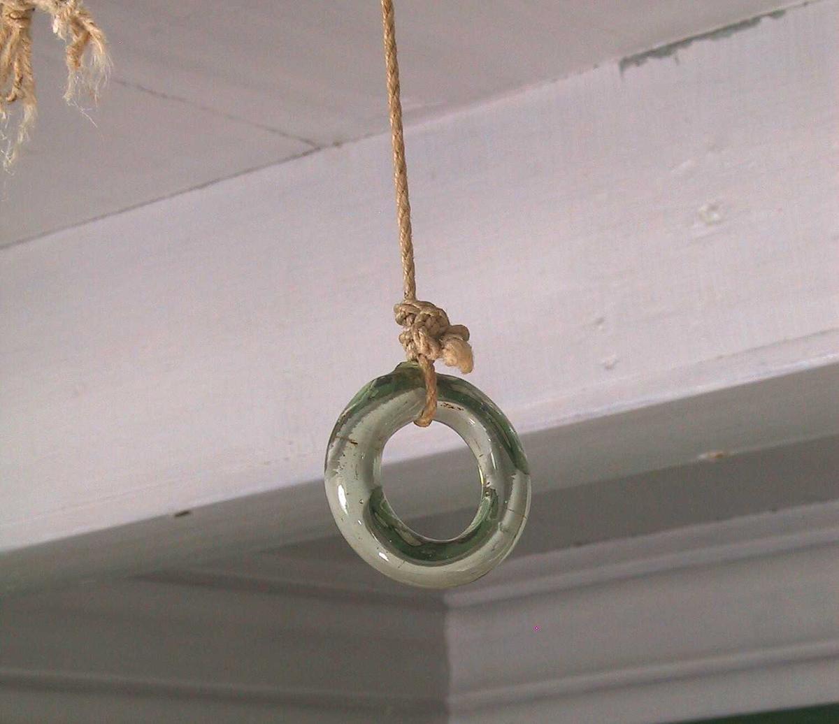 Ringeklokke plassert i kjøkkenet, med glassring under taket i dagligstuen, rommet ved siden av.  Jern, aluminiumsmalt.  Liten klokke med dråpeformet knevel, festet i buet flat jernstang med snor festet i taket inn til dagligstuen, h av en ring (nedre del avbrukket). Tilstand: rust under malingen.