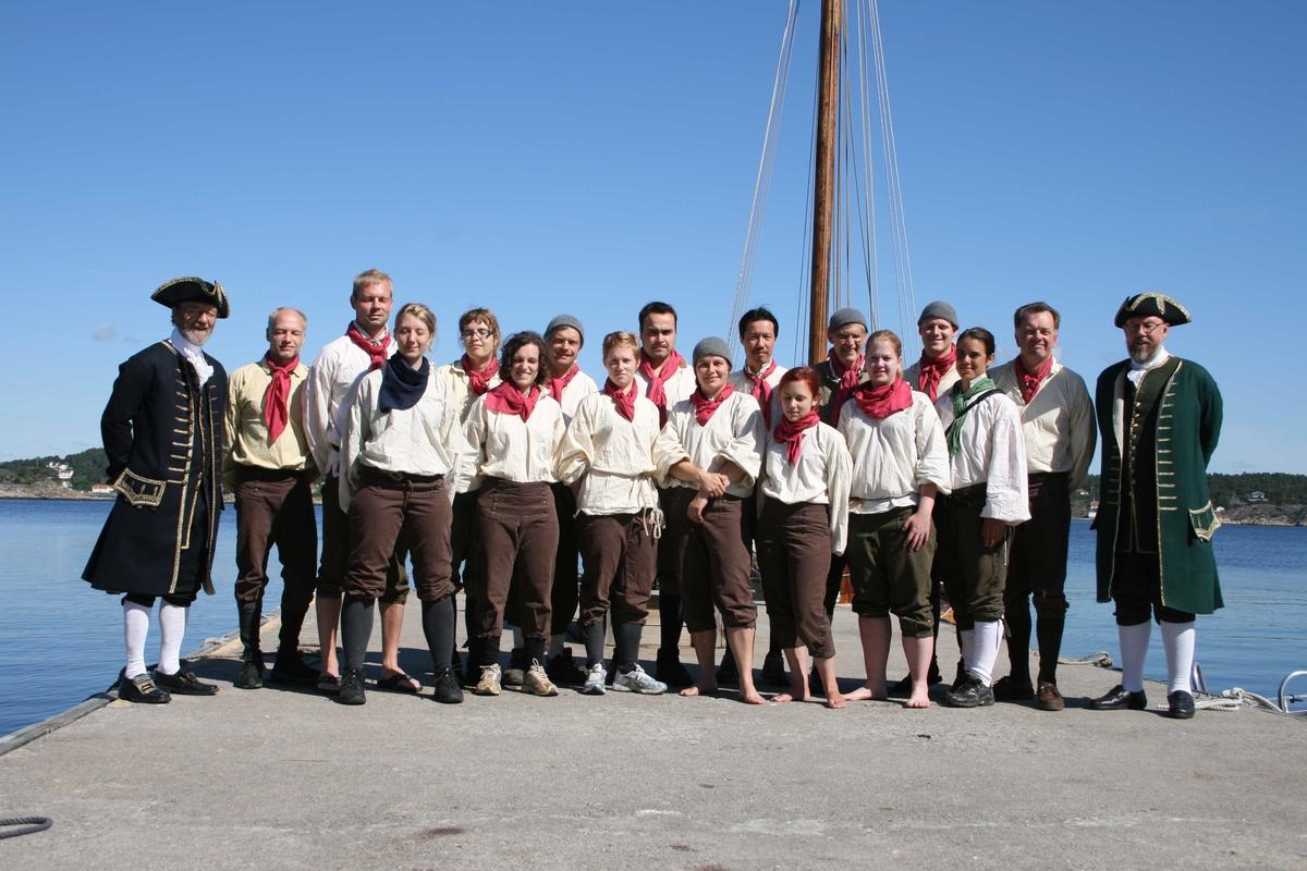 Merdøgaard. En del av mannskapet, flankert av kaptein og styrmann, på skipet Götheborg poserer på brygga på Merdøgaard ette ankomst.    Skipet besøkte Arendal i anl. Kjæmpestaden, og lå flere dager på Revesandsfjorden.