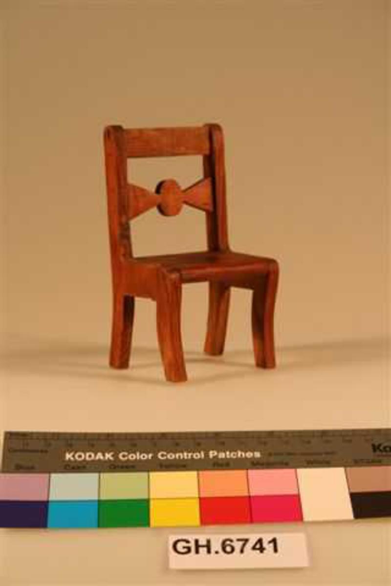 Enkel stol med rett rygg. En tverrsprosse med utbukning i ryggen. Minner om enkle møbler i biedermeierstil.