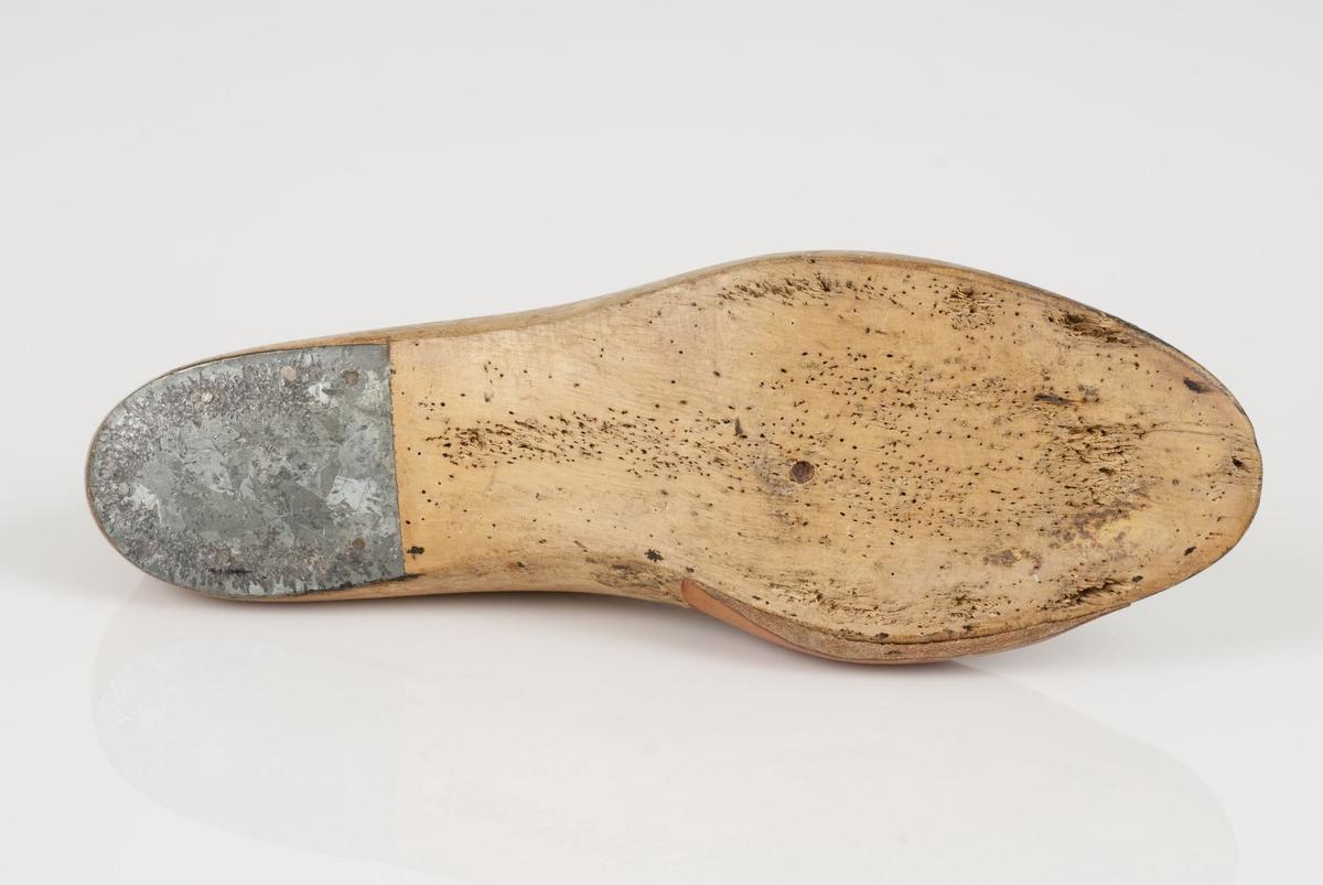 En tremodell i to deler; lest og opplest/overlest (kile). Høyrefot i skostørrelse 41, og 8,5 cm i vidde. Hælstykke av metall. Lestekam av skinn