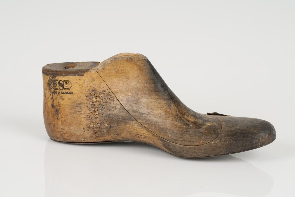 En tremodell i to deler; lest og opplest/overlest (kile). Venstrefot i skostørrelse 46. Såle av metall. Lestekam av skinn.