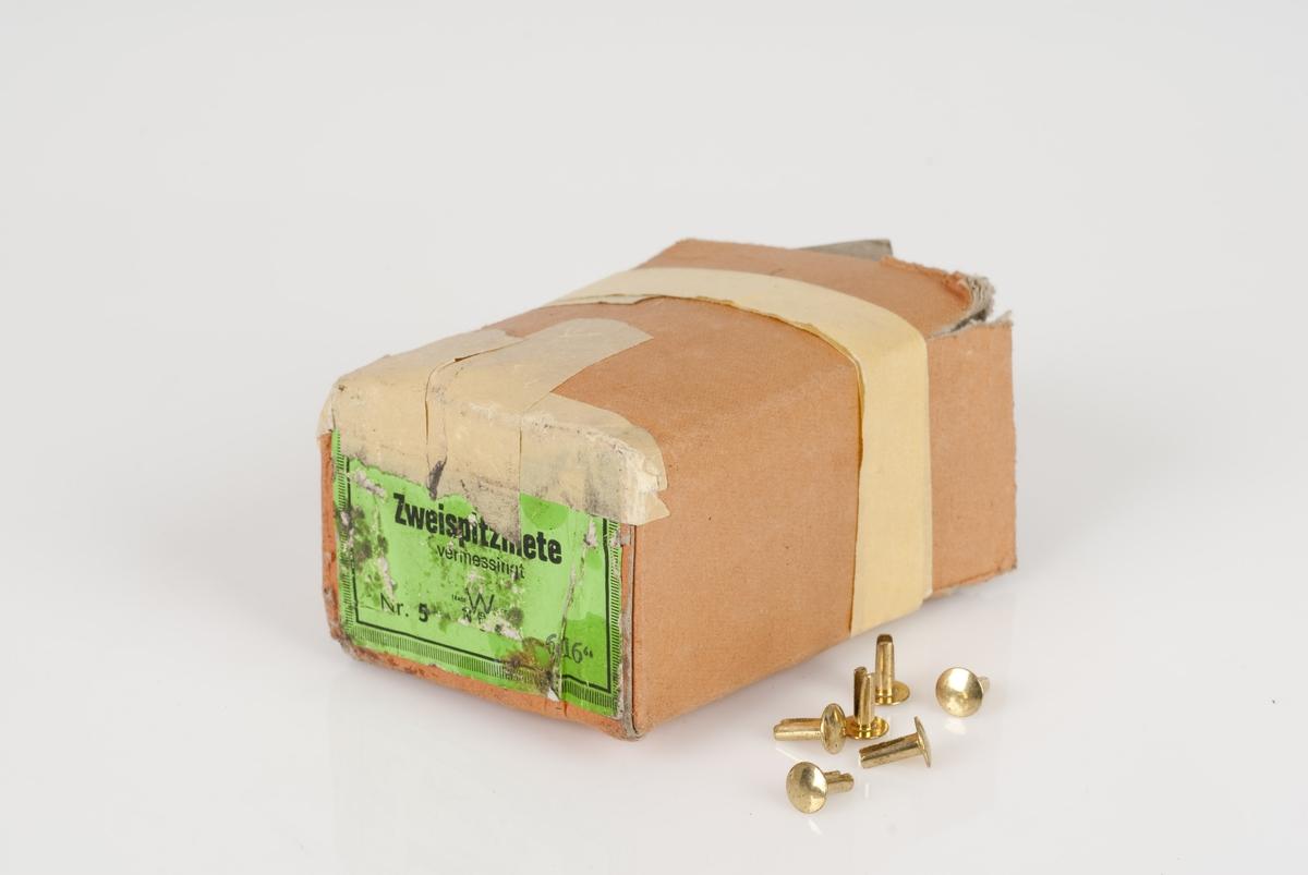Splittnagler av metall i en pappeske. Splittnaglene er i gullfarge. Grønn merkelapp med påført tekst på bunnen av esken.