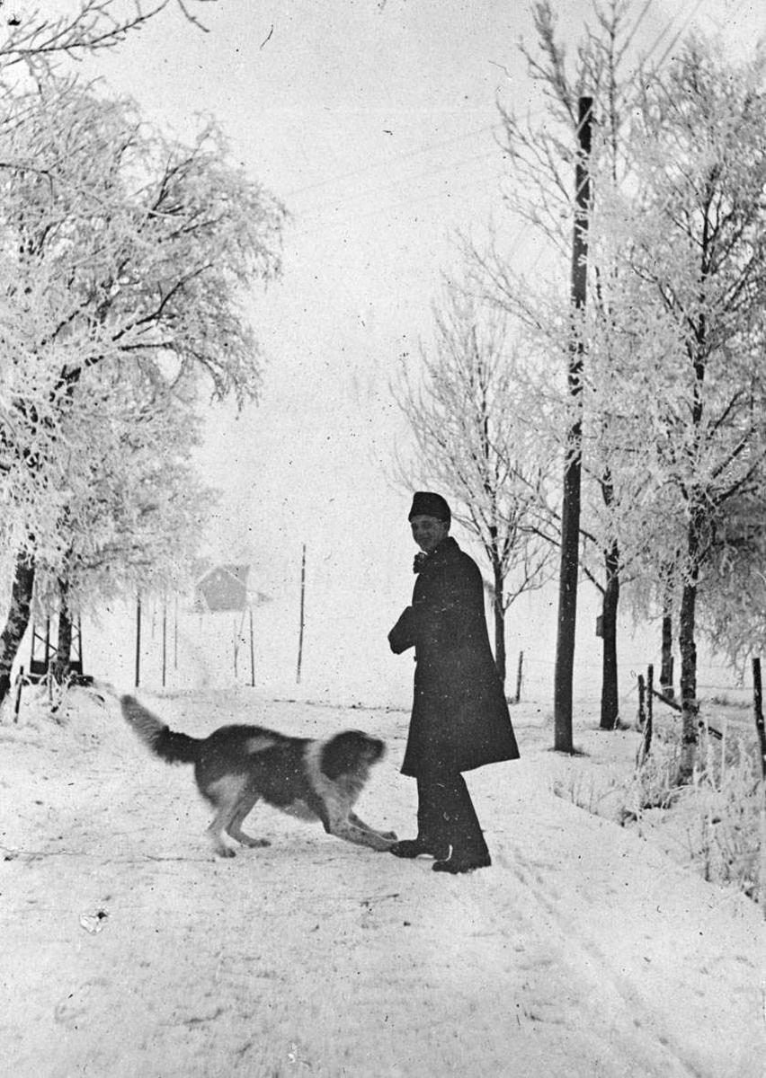 Vinterkledd mann leker med hund i Bjastadbakken, snølandskap