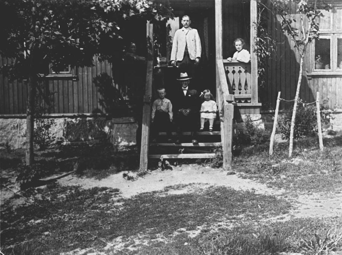 Familiebilde på storstuetrapp på våningshus på gard.