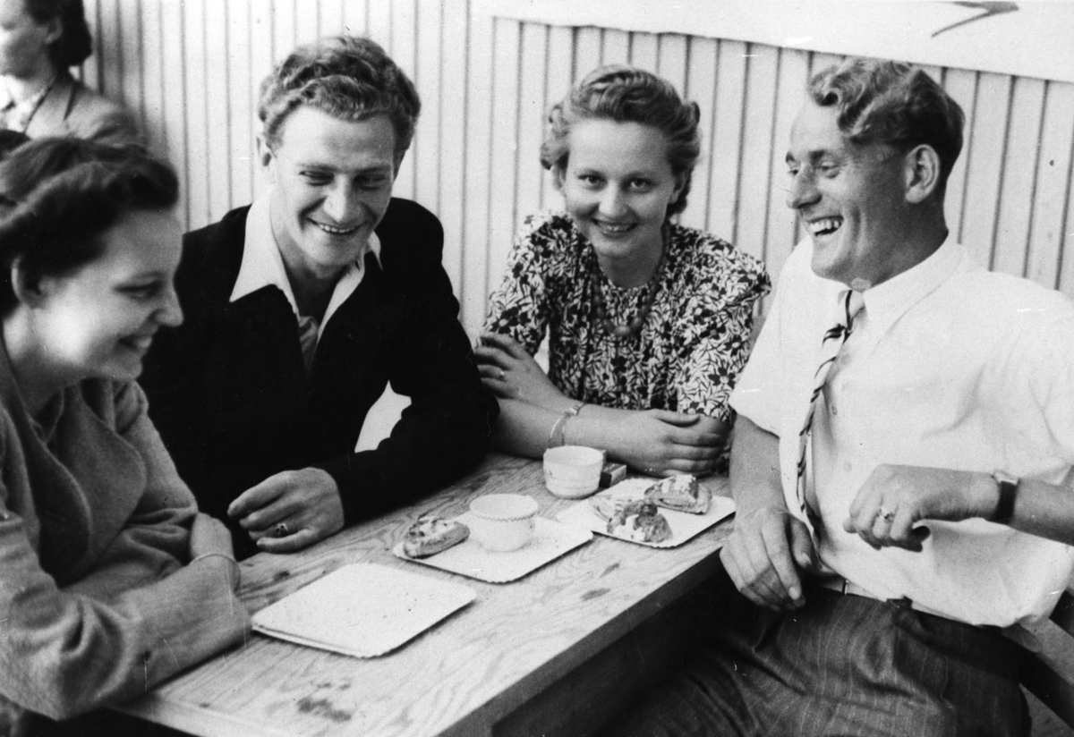 Fire mennesker ved et bord. Feiring av freden.
