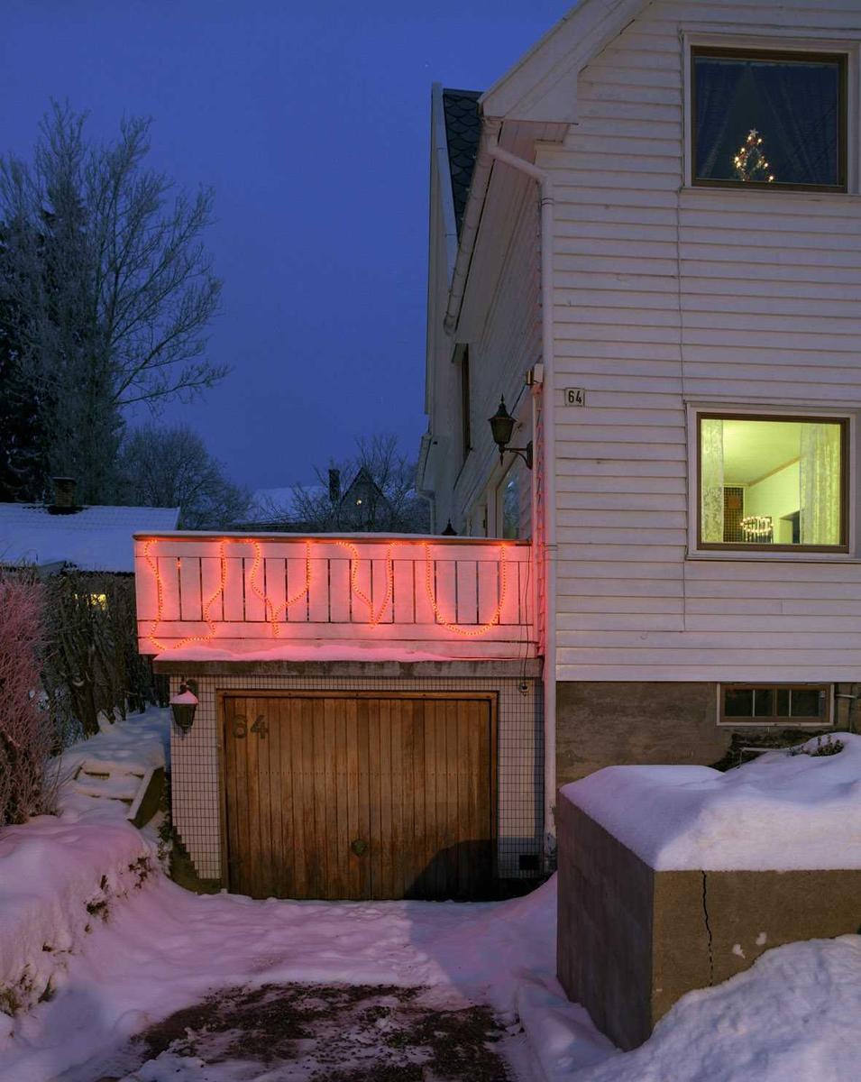 Julebelysning.  Rød lysslange hengt på veranda på enebolig.