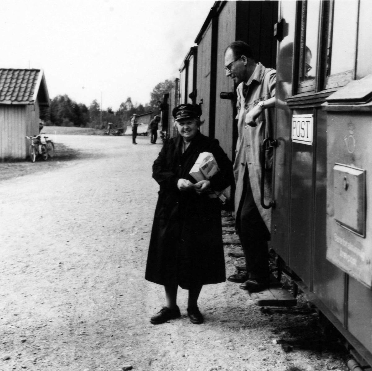 Stasjonsmester og overpostpakkemester utveksler meldinger under oppholdet på Hornåseng stasjon.Overlevering av dagens post.