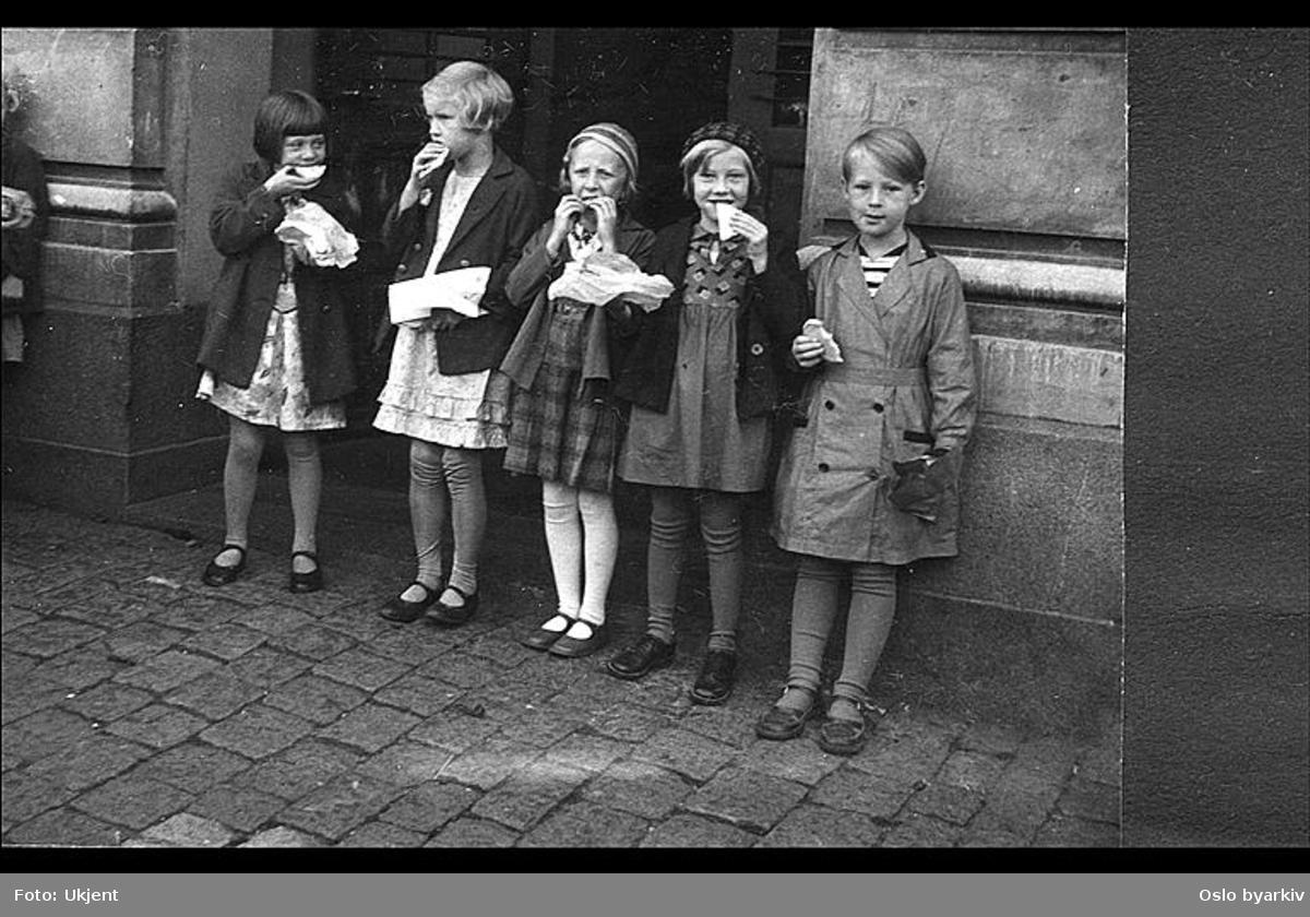 """Gruppebilde av piker som spiser matpakke i skolegården. Albumtittel: """"Sofienberg skole femti år - første september 1933."""""""