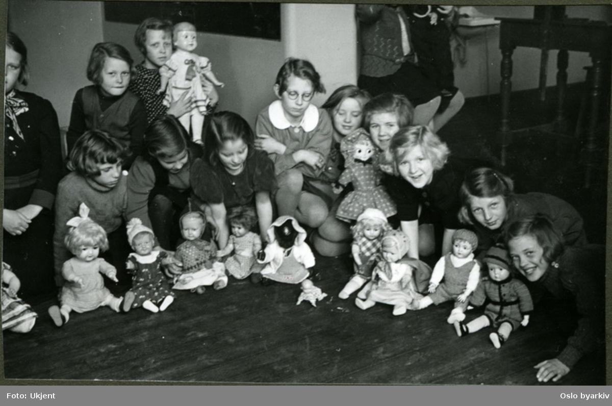 """Jenter som viser fram sine dukker. Albumtittel: """"Sofienberg skole femti år - første september 1933."""""""