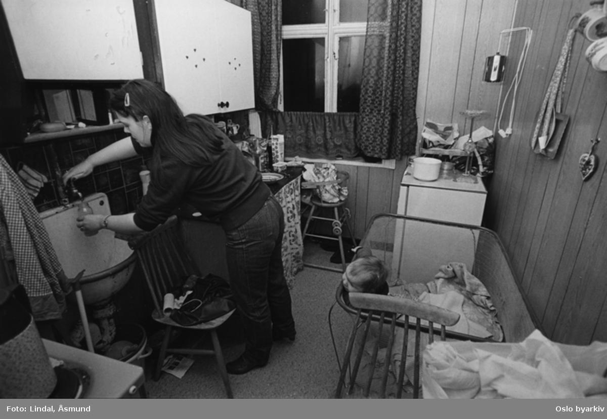 Kvinne på kjøkkenet med spedbarn i en lekegrind. Fotografiet er fra prosjektet og boka ''Oslo-bilder. En fotografisk dokumentasjon av bo og leveforhold i 1981 - 82''. Kontakt Samfoto ved ev. bestilling av kopier.