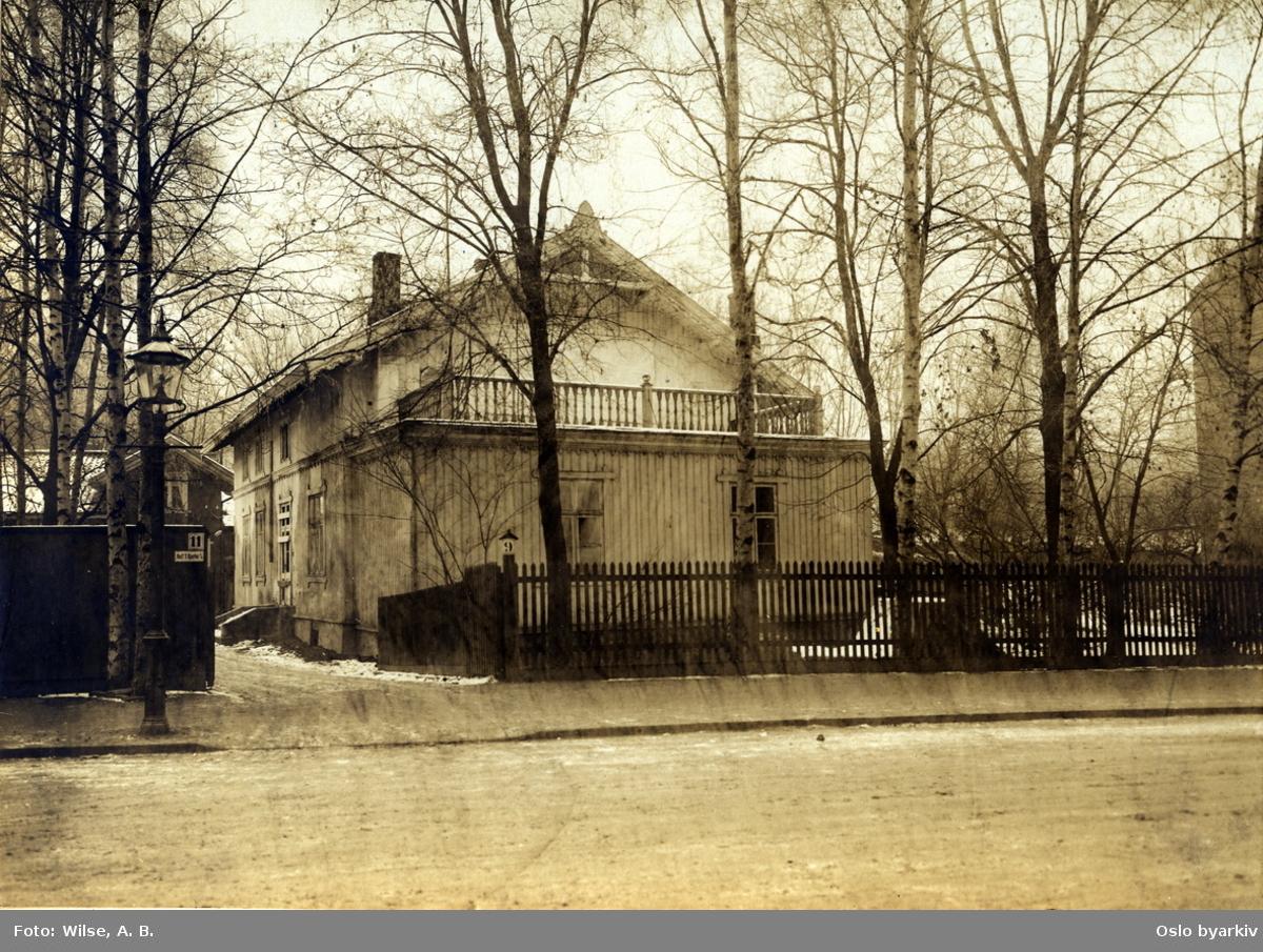 """Trevilla (Trehusbebyggelse) i Neuberggata. Gatebelysning. Stakittgjerde. Navneskilt på gjerde: """"Rolf T. Bjerke A/S"""". (Neuberggata 11.)"""