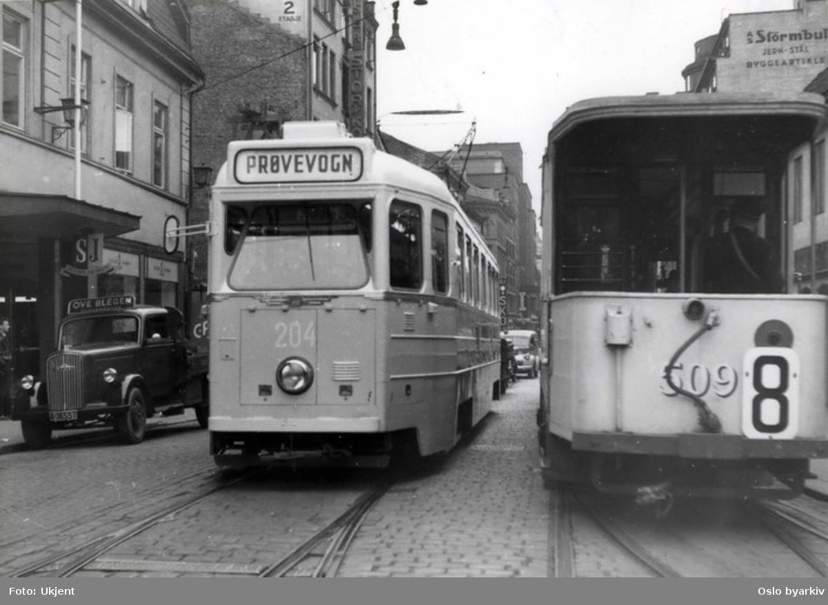 Oslo Sporveier. Høkatrikk motorvogn 204 (fra 1952) under prøvekjøring i Storgata. Tidligere Grønntrikk, motorvogn 509 (fra ca. 1922) på linje 8, Stortorvet-Sagene over Grünerløkka (1954-1957). Firmabil tilhørende Ove Blegen glassmesterforretning i Storgata 4. Storgata 3 til venstre. Bildet fra 1950-tallet.