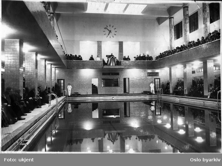 Åpningstale for svømmehallen i Torggata bad. Svømmehallen ble tatt i bruk første desember 1931. Grunnsteinen ble lagt første september 1924. Badet ble bygget i tre etapper hvorav første etappe besto av fløyen mot Badstugata, andre etappe var hovedfasaden og fløyen mot Vaskeribakken (Hammersborggata). Tredje etappe besto av svømmehallen med tilliggende rom. Under talestolen på femmeteren ses kontrollrommet for svømmehallen.