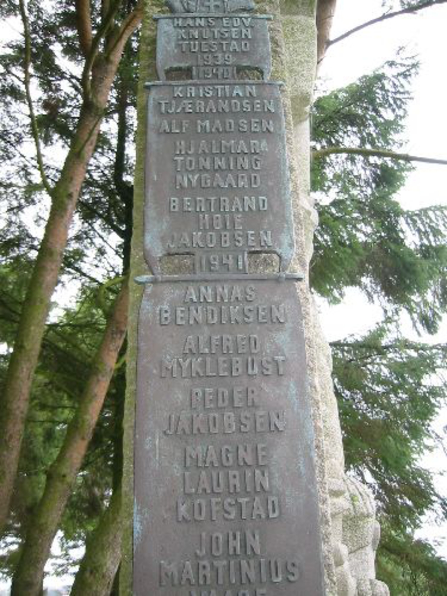 Bautaen står på en høyde inne på kirkegården. Det er trapper opp til bautaen. Rundt bautaen er det hellelagt. Bautaen er h 3,40 b 1,30 d 0,50. Hellelagt 2,5 x 2,5 m. I frontene er det gigurer av far og barn med båter og sjø, og en engel svever over. På den ene siden er det oppsatt et vikingskip i bunnen med segl over hverandre med navnene på de som falt fra i krigen. På den andre siden er det en sirkelrun bronse plate med bilde av Heming Skree. I sirkel rundt er det ett dikt.