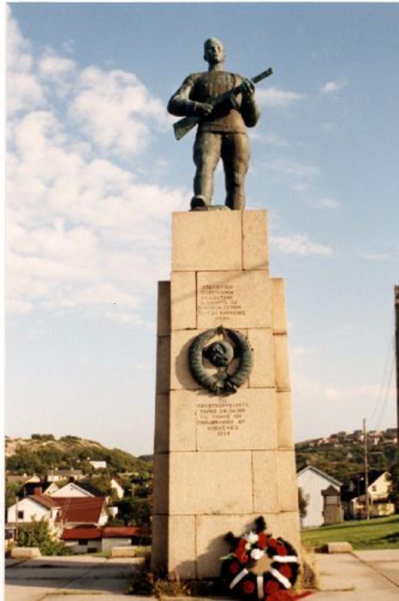 Russermonumentet i Kirkenes. Sokkel av steinblokker med soldat i bronde på toppen. Soldaten er ca 2 m høy og står på en steinsokkel 3,5 x 1,3 m. Monumentet har både norsk og russisk tekst.