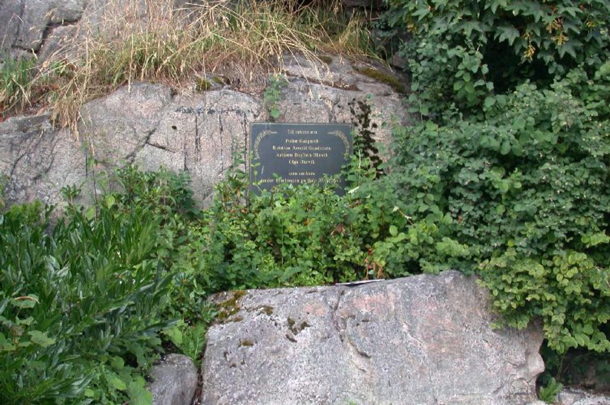 Kopperplate med inskripsjon montert på fjell.